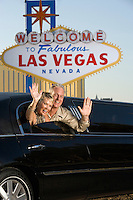 Middle-aged couple sitting in limousine and waving in front of Welcome to Las Vegas sign