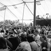 Crowd sitting down in a tent and watching a performance, Glastonbury, Somerset, 1989