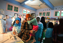 A young girl is comforted by her mother after being circumcised in Bandung, Indonesia on April 23, 2006.  The families of 248 girls were given money to have their children circumcised in a mass circumcision celebration timed to honour the Prophet Mohammed's birthday. While religion was the main reason for circumcisions, it is believed by some locals that a girl who is not circumcised would have unclean genitals after she urinates which could lead to cervical cancer. It is also believed if one prays with unclean genitals their prayer won't be heard. The practitioners used scissors to cut the hood and tip of the clitoris. The World Health Organization has deemed the ritual unnecessary and condemns such practices.