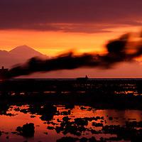 Gili Trawangan, Indonesia: il forte vento trasporta il fumo proveniente da un fuoco acceso sulla spiaggia dell'isola.<br /> <br /> Gili Trawangan, Indonesia: fire smoke from the beach is spread by strong wind at sunset