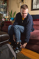 Nick Rhoades plugs in his ankle bracelet to charge in his house in Waterloo, Iowa on Thursday, November 7, 2013.