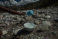 RENDEL, HAITI - OCTOBER 12, 2016: A woman collects drinking water from the river that runs along the village of Rendel, and is believe to be contaminated and spreading Cholera. A week has passed since Hurricane Matthew tore through this remote stretch of Haiti's southern peninsula, leaving an apocalyptic landscape of treeless countryside, disarticulated homes and a land stripped of its natural riches.  But for many, the torment has only started.  What began as a small cholera outbreak in the mountains before the hurricane has now spread into every crevice of this valley and the hills above. First came the sick, who trudged down to Rendel in search of medical care, bringing the disease with them. Then, when the floods came, cholera was carried down by the water itself, which swept up fecal matter dumped on the hillsides, contaminating the river and other drinking supplies.  Water unboiled or unchlorinated and poor hygiene meant the infections spread rapidly.  PHOTO: Meridith Kohut for The New York Times
