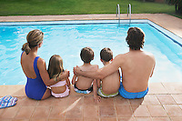 Family with three children (6-11) sitting by pool back view