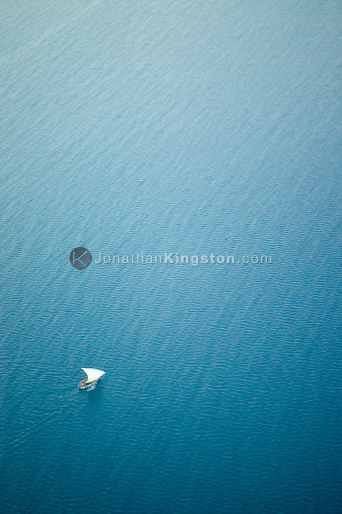 An aerial view of a small dhow, a carved wooden boat, making its way between Dar es Salaam, Tanzania and Stonetown, Zanzibar, on the Indian Ocean.