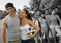 Happy couple holding soccer ball enjoying with friends at park