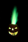 A carved pumpkin is set on fire.  The green flame is made by adding copper chloride to the flame inside the pumpkin.