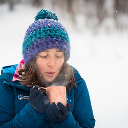 A woman enjoys a hot beverage while winter camping in New Hampshire's White Mountains. Randolph Community Forest.