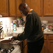 Reggie Griffin fixing dinner consisting of baked beans with hot dog and a salad. John E. Johnson, who is not eligible for medicaid, receives services for 12 hours per week through Illinois&rsquo; Community Care Program. Johnson worries his services will be cut if the state transition seniors like him to a new program. The state employs Reggie Griffin to help Johnson with daily chores so he is able to stay in his home, as opposed to going to an nursing home. <br /> Photography by Jose More