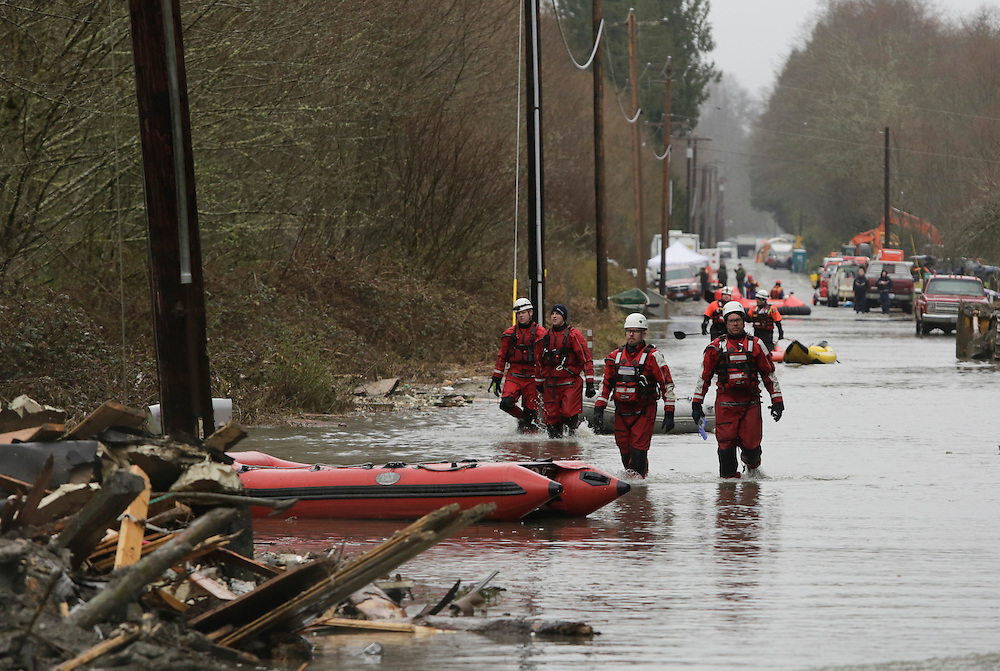 Swift water teams head into flood waters on Highway 530 as search work continues in the mud and debris from a massive landslide that struck Oso near Darrington, Washington March 29, 2014. The grim task of combing through debris from a landslide that sent a wall of mud cascading over dozens of homes on the outskirts of a rural Washington town came to a standstill briefly on Saturday for a moment of silence.The somber moment at 10:37 a.m. (1737 GMT) was observed exactly one week after the catastrophe, amid uncertainty over the fate of 90 people still listed as missing. On Friday, the unofficial body count rose to 27.  REUTERS/Jason Redmond (UNITED STATES)