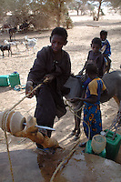 Niger, Agadez, Tidene, 2007. Lowering the buckets into this Tuareg well  is done by hand, as they are raised when full by donkeys.