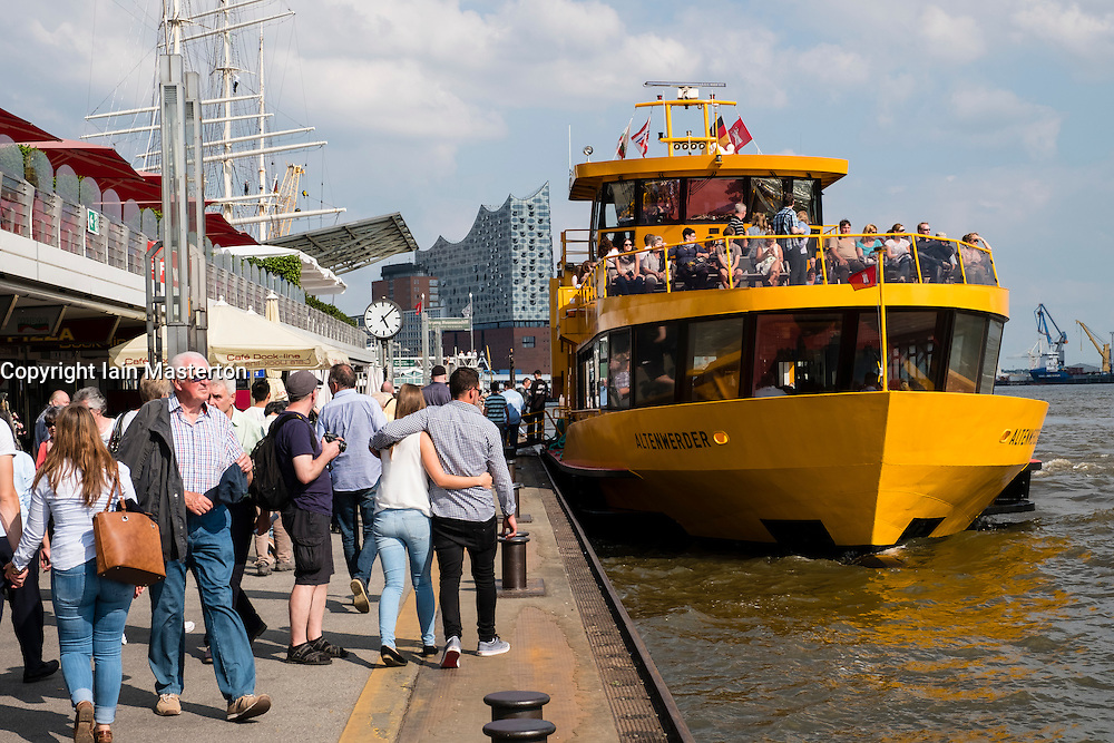 View of busy ferry and tour boat landing jetties, Landungsbrucken,  in port of Hamburg Germany