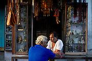 A gift shop merchant chats as the sun sets on Varanasi, India.