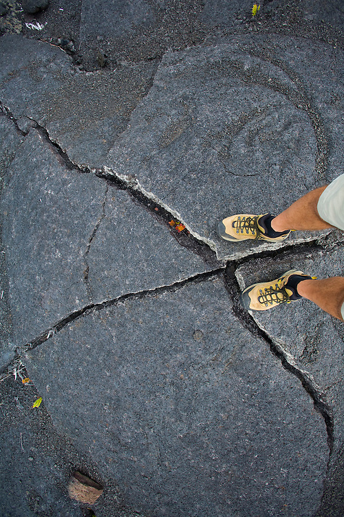 A man's feet and legs standing on an upheaval in an old lava flow in Hawai'i Volcanoes National Parks