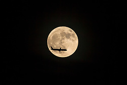 An aircraft descending for London Heathrow is silhouetted against the rising moon. London, December 22 2018.