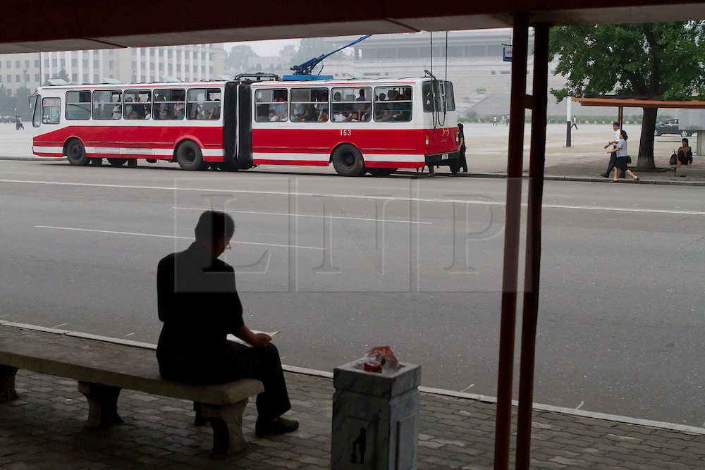 © Licensed to London News Pictures. 10/08/2011. Pyongyang, North Korea. A man waits for a bus at a bus stop in Kim Il Sung square.  Pyongyang has an extensive network of trams, and buses powered by overhead cables, with few petrol powered buses as fuel is very expensive in North Korea. Photo credit : James Gourley/LNP/