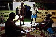 Cérémonie coutumière de préparation de demande de mariage à Maré.<br /> Lorsqu'un mariage est prévu dans la tribu, le clan de l'époux fait tout d'abord « passer la paille » pour que tous les clans alliés se réunissent à une certaine date autour du chef de clan. Ils offrent alors une participation en argent afin de rassembler un don suffisant pour faire la demande de mariage, c'est-à-dire « réserver » ou « attacher la main » de la femme auprès de son clan et de ses oncles maternels. Une comptabilité stricte permet de répartir l'argent qui sera réservé au chef de clan ou aux oncles maternels qui feront la demande à la femme, ainsi qu'à sa famille.<br /> Échange coutumier sous le regard d'André Cinédrawa (frère du futur époux). Il est l'ainé qui ira faire la demande. Tribu de Rawa – District de Laroche- Maré, Îles Loyauté, Nouvelle-Calédonie - Avril 2014.