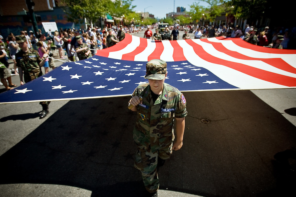 JEROME A. POLLOS/Press..Luke Glendening, a member of the Civil Air Patrol, helps carry the flag down Sherman Avenue during Wednesday's parade.