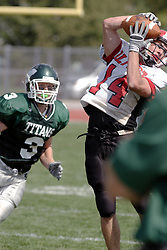 09 September 2006 Comet's Carl Mulder grabs a pass as it hits his helmut and Titan Eric Esch meets up with Mulder..In the first ever football competition between the Olivet Comets and the Illinois Wesleyan Titans, the Titans strut off the field with a 21- 6 victory. .Game action took place at Wilder Field on the campus of Illinois Wesleyan University in Bloomington Illinois.