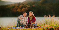 Roanoke tourism; Couple having a romantic  picnic by lake in the fall.