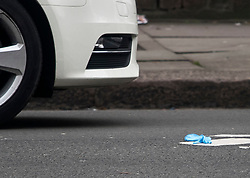 © Licensed to London News Pictures. 21/02/2018. London, UK. A medical glove lies on the floor next to an abandoned car at the scene on Malden Road, Camden, where one of two stabbings took place yesterday evening, killing two young men. Police were called to a second disturbance in the area, in which a second man was stabbed to death, and are currently investigating if the two incidents are connected. Photo credit: Ben Cawthra/LNP