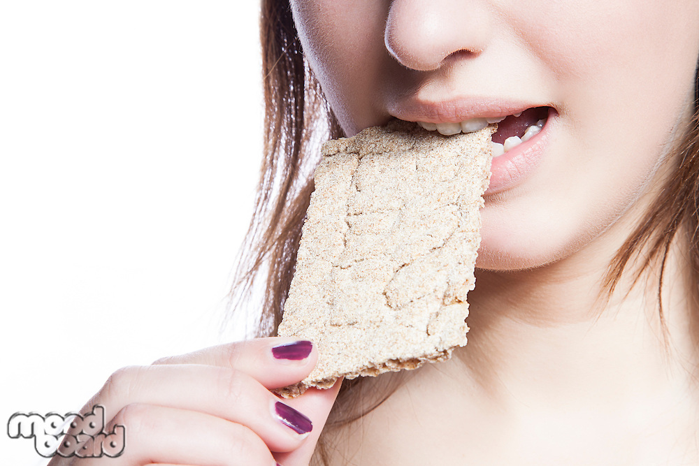Detail shot of woman eating crispbread over white background