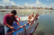 Man painting his boat on Guadalquivir river.