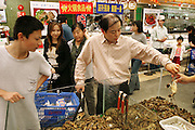 During their expedition to Ito Yokado, a Japanese supermarket chain, the Dongs of Beijing, China, inspect a tray of live crabs. In many restaurants and markets in China, much of the seafood is sold live as a guarantee of freshness. Hungry Planet: What the World Eats (p. 80). The Dong family of Beijing, China, is one of the thirty families featured, with a weeks' worth of food, in the book Hungry Planet: What the World Eats.
