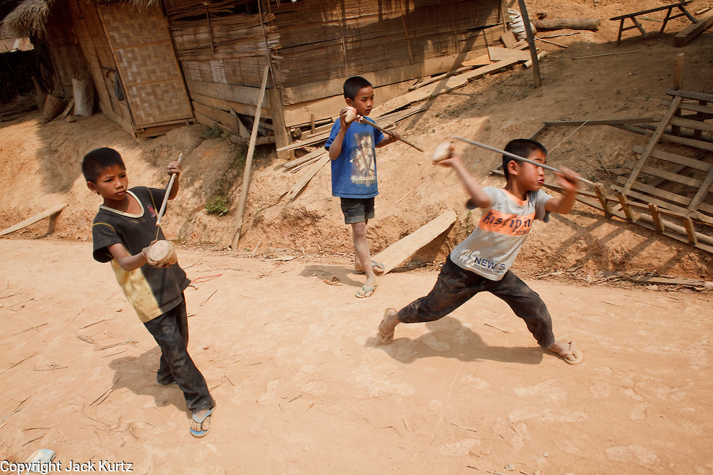 Mar. 16, 2009 -- LUANG PRABANG, LAOS: Children play with their tops in a village on Highway 13 south of Luang Prabang, Laos. Highway 13 is the main highway in Laos and carries tourist and truck traffic between the capital Vientiane and Luang Prabang. Photo by Jack Kurtz