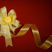 Golden bow and ribbon against a red background. Center of bow is key lighted and light falls away in rest of frame.