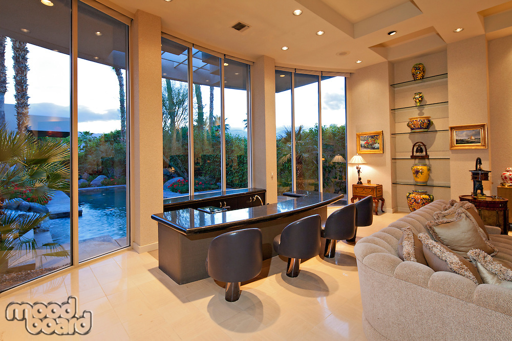 Chairs along counter near window in living room of mansion