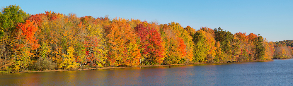 Early morning sun lights up the shoreline of the Clear Fork reservoir and marina during peak autumn color. Panoramic format.