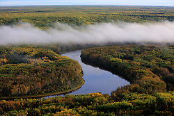 CANADA ALBERTA FORT MCMURRAY 28SEP09 - Ground fog over the river Athabasca during early morning, north of Fort McMurray, northern Alberta, Canada...The tar sand deposits lie under 141,000 square kilometres of sparsely populated boreal forest and muskeg and contain about 1.7 trillion barrels of bitumen in-place, comparable in magnitude to the world's total proven reserves of conventional petroleum. Current projections state that production will  grow from 1.2 million barrels per day (190,000 mÃ,³/d) in 2008 to 3.3 million barrels per day (520,000 mÃ,³/d) in 2020 which would place Canada among the four or five largest oil-producing countries in the world...The industry has brought wealth and an economic boom to the region but also created an environmental disaster downstream from the Athabasca river, polluting the lakes where water and fish are contaminated. The native Indian tribes of the Mikisew, Cree, Dene and other smaller First Nations are seeing their natural habitat destroyed and are largely powerless to stop or slow down the rapid expansion of the oil sands development, Canada's number one economic driver...jre/Photo by Jiri Rezac / GREENPEACE..© Jiri Rezac 2009