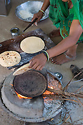 Vasanben making chapatis on an open wood fire at their home in Ahmedabad, India.