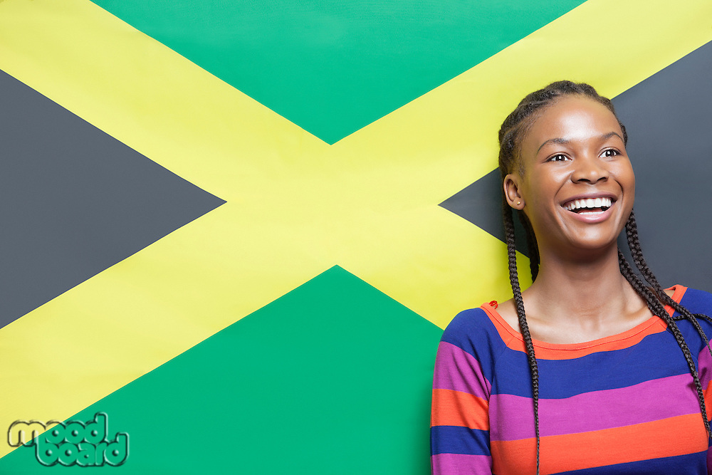 Excited young woman with braided hair against Jamaican flag