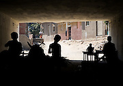 Boys on a horse and cart are silhouetted in a tunnel under a motorway in Old Cairo, Egypt. Children often help their parents in working along side schoolwork.