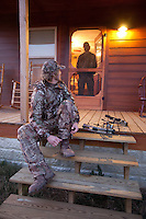 hunter putting on his boots in hunting camp