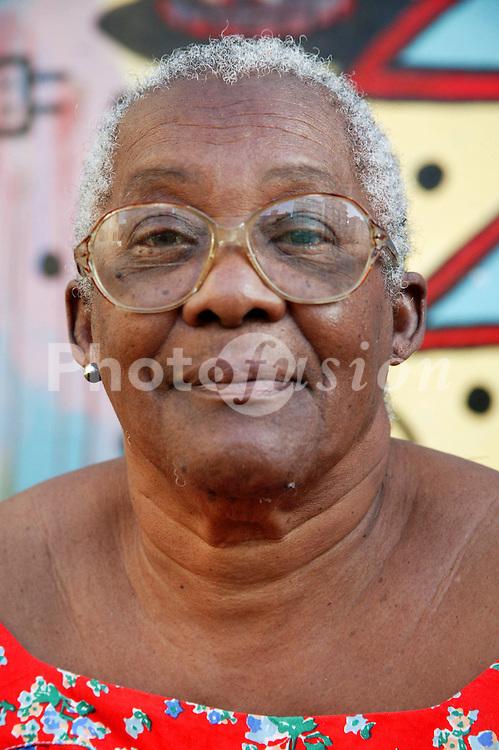 Elderly black woman sitting in front of mural; Havana; Cuba,