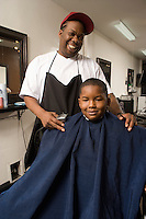 Young boy and barber together in the barbers