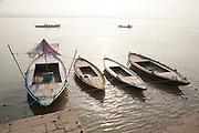 Rowing boats tied up on the river Ganges at Varanasi, Uttar Pradesh, India