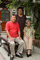 On October 1st 1949 Tong Mingkuan, 84,  was in the courtyard near Gulou where she'd been living for two years and where she still lives today taking care of her two children who are with her in the picture. Beijing 2009.