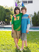 Portrait of two boys (10-12) in party hats in yard