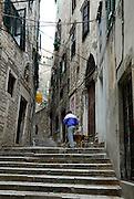 Man walking dog, backstreets of Sibenik, Croatia