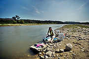 Luisa Jimenez does her washing at the river.