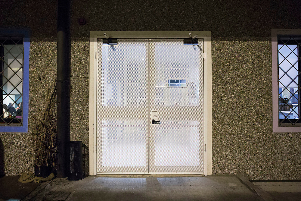 """MILANO, ITALY - 1 MARCH 2016: The entrance door of the """"InGalera"""" restaurant, which resembles a prison cell gate, is here at the Bollate prison in Milan, Italy, on March 1st 2016.<br /> <br /> """"InGalera"""" (which translates in English as """"InJail"""") is the first restaurant located inside a prison and offering high-quality cooking to the public and a future to the inmates. It was inaugurated last October inside the Bollate prison in Milan. It is open five days a week for lunch and dinner, and seats 55 people. There are 9 people involved in the project, including cooks and waiters, all regularly employed and all inmates of the prison, apart from the chef and the maître d'hôtel, recruited from outside to guarantee the high quality of the food served. The restaurant is a project of the co-operative ABC La Sapienza - that operates inside the prison and provides more than 1,000 meals three times a day with the help of inmates they've hired - and of PwC, a multinational operating in the field of corporate consultancy. The goal of this project is to follow prisoners in rehabilitation process of social inclusion.<br /> <br /> The Bollate prison is already known for being a good example of penitentiary administration. The inmates are free to move around from one area to the other inside the prison (their cells open at 7:30am and close at 9pm) to go study, exercise in a gym, or work (in a call center, as scenographers, tailors, gardeners, cooks, typographers, among others)  in one of the 11 co-operatives inside the prison or in one of the private partnering businesses outside the prison. The turnover of the co-operatives that work inside the prison was €2mln in 2012."""