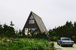 A frame beach house with a Mustang car in the driveway in Amagansett, NY