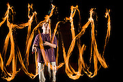 Boy juggling three flaming torches.