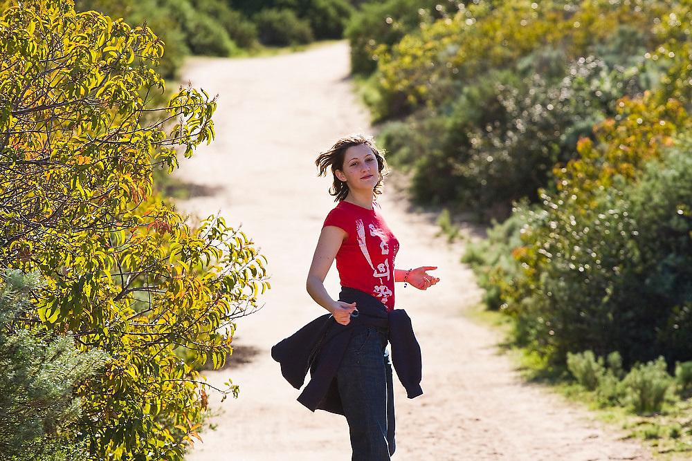 A young woman turns around to look at the camera as she walks down a dirt road in Crystal Cove State Park, California.