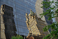 NYC, New York, U.S.  21st May 2013. An ornate building is reflected on the vast curved facade of an office building, during a pleasant spring day, with a high of 86ºF/32ºC in Manhattan.