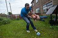 Simon Giles plays with his son Oliver-James outside the house the family rents in Bradford, Great Britain Monday, May 26, 2014. Through Save the Children's EAT, SLEEP, LEARN AND PLAY programme the family was awarded a fridge freezer and a toy and book pack. A record five million children in the UK could be trapped in poverty by 2020, according to new research by Save the Children. The report reveals that children have paid the highest price in the recession, with families having been hit by years of flat wages, cut to benefits and the rising cost of living. (Elizabeth Dalziel for Save the Children )