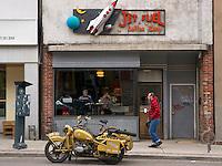 A restored World War 2 era BMW R75 parked in front of a coffee shop.